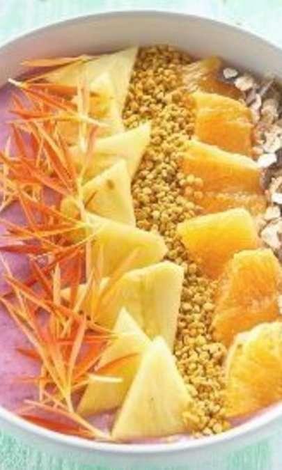 Bowl ai frutti rossi con topping di ananas, arancia rossa,  polline e muesli