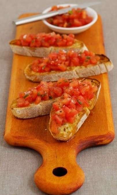 Bruschetta con pesto di aglio, pomodori, rucola e mozzarella